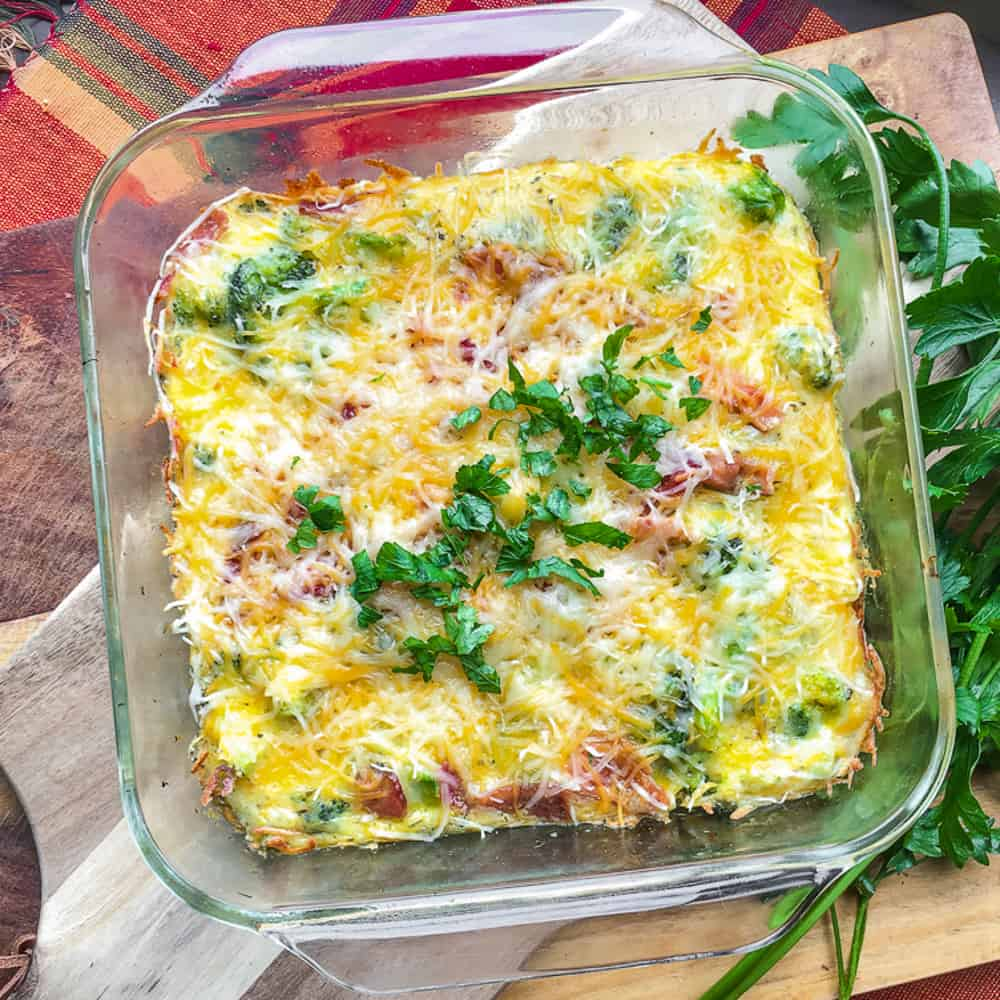Pan of egg casserole, topped with bacon and cheese garnished with parsley.
