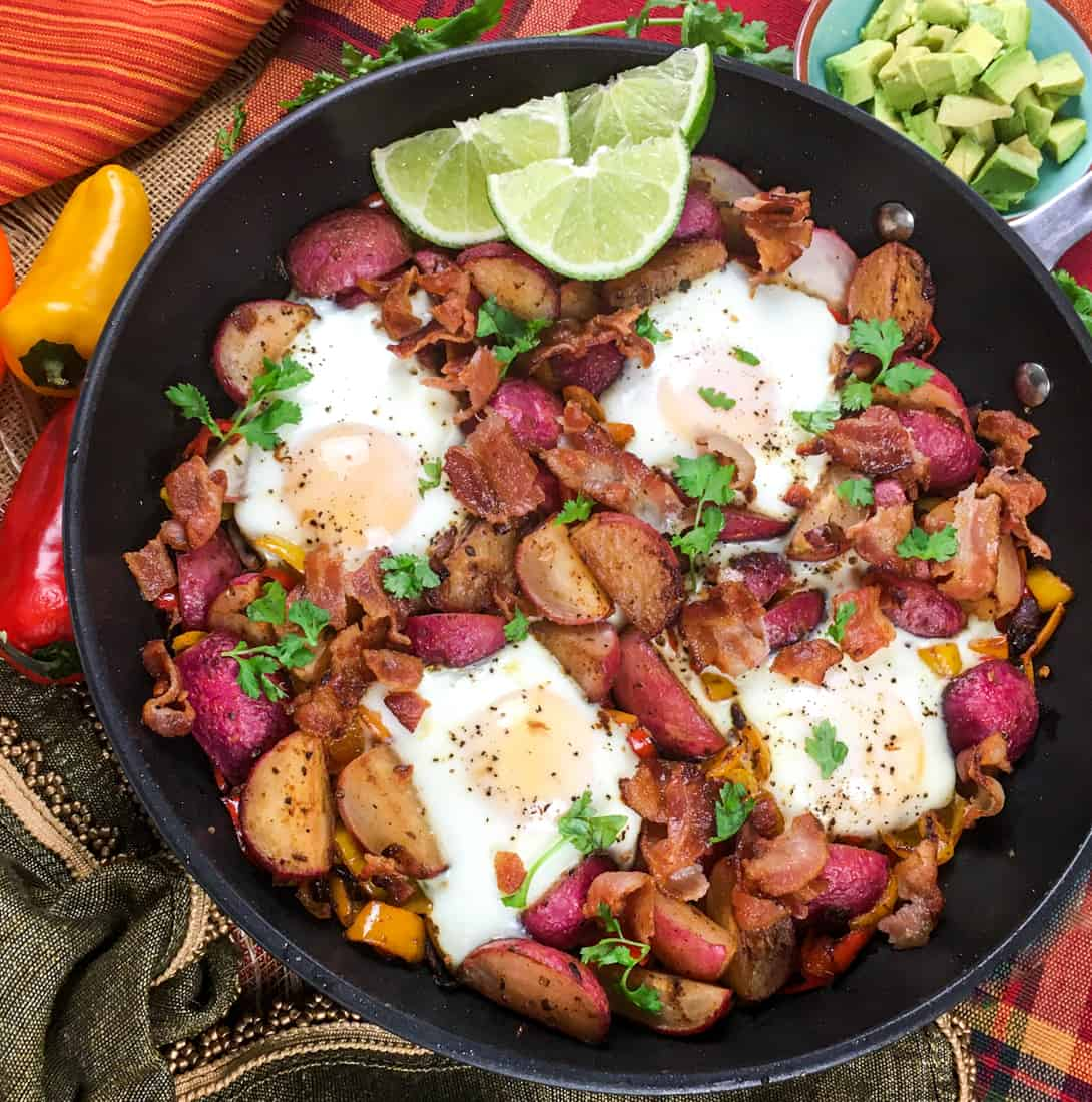 cast iron skillet filled with eggs, radish, bacon and cilantro.