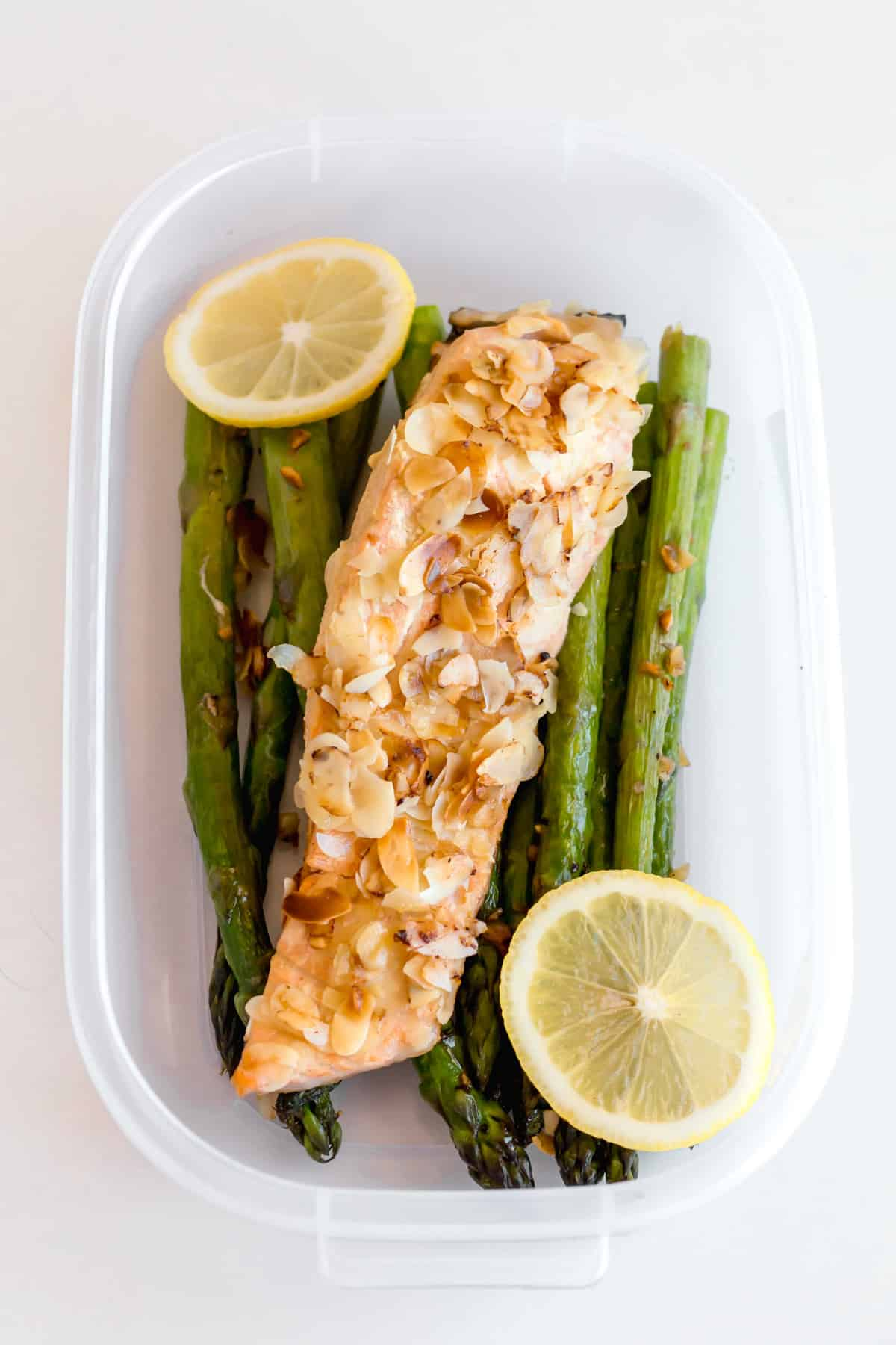 salmon and asparagus in plastic ware to demonstrate easy portable keto lunch leftovers
