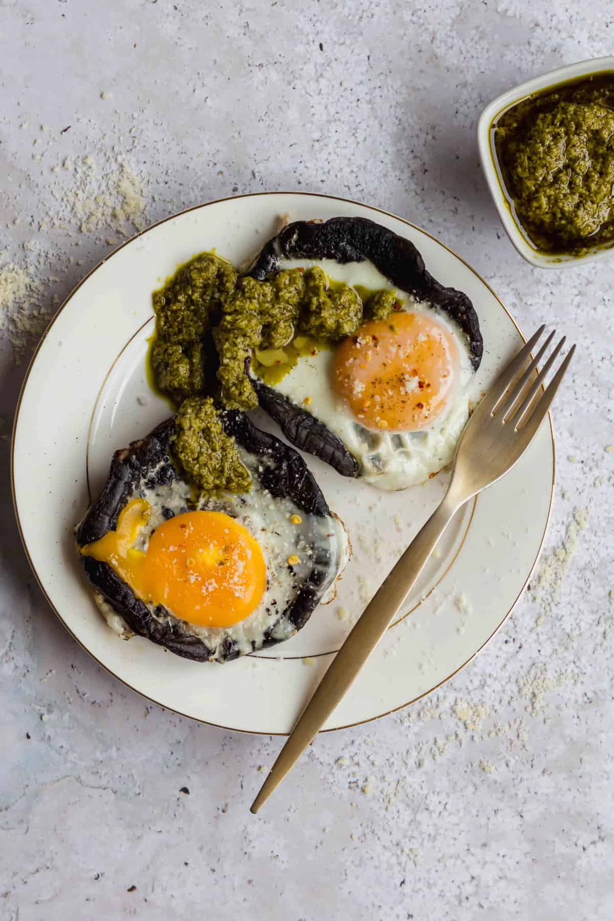 2 portobello mushrooms stuffed with fried eggs on plate with pesto sauce and fork